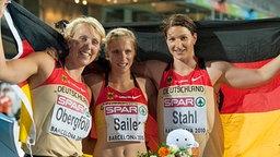 Die deutschen Speerwerferinnen Christina Obergföll (l, Silber) und Linda Stahl (r., Gold) sowie die Sprinterin Verena Sailer (100m, Gold) posieren mit der deutschen Fahne.